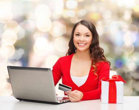 holiday spending: christmas, holidays, technology and shopping concept - smiling woman with credit card, gift box and laptop computer over lights background
