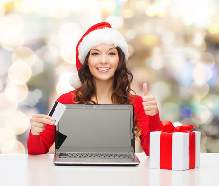 approvement: christmas, holidays, technology and shopping concept - smiling woman in santa helper hat with credit card, gift box and laptop computer showing thumbs up gesture over lights background