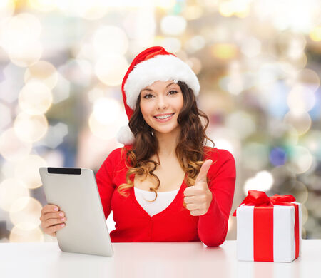 approvement: christmas, holidays, technology, gesture and people concept - smiling woman in santa helper hat with gift box and tablet pc computer showing thumbs up over lights background