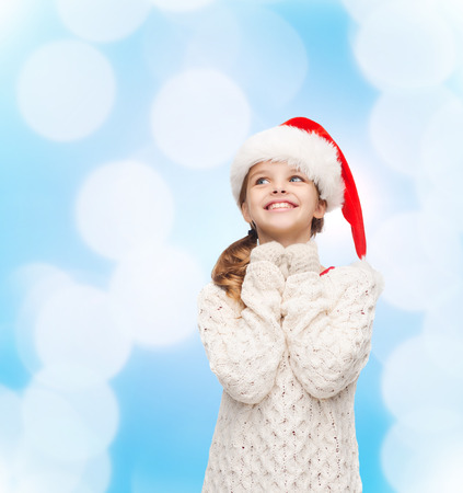 christmas, holidays, childhood and people concept - smiling girl in santa helper hat over blue lights background photo