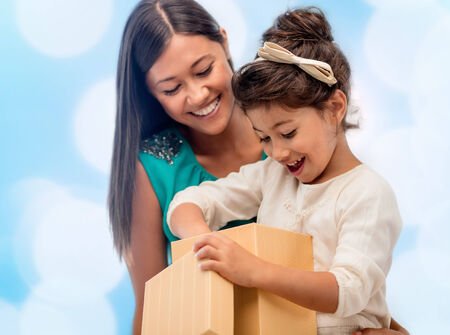 niños latinos: navidad, días de fiesta, celebración, la familia y las personas concepto - feliz madre y el niño de la muchacha con caja de regalo sobre luces azul de fondo