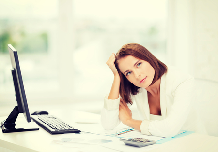 business, education and technology concept - stressed businesswoman with computer, papers and calculator in office photo