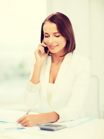 business, education and technology concept - smiling businesswoman with smartphone papers and calculator in office photo