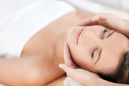 dayspa: health, beauty, resort and relaxation concept - beautiful woman in spa salon getting face treatment Stock Photo