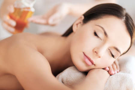 closed eye: beauty and spa concept - beautiful woman in spa salon getting oil treatment Stock Photo