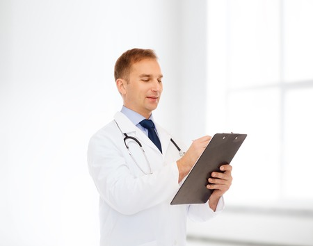 medicine, profession, workplace and healthcare concept - smiling male doctor with clipboard and stethoscope over white room background photo