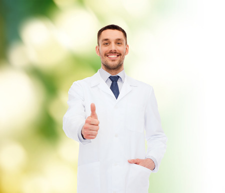 healthcare, profession and medicine concept - smiling male doctor showing thumbs up over white background photo