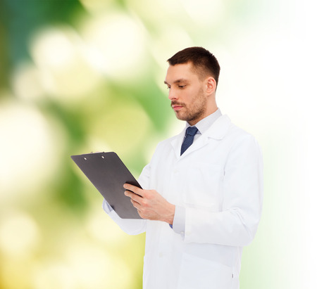 taking medicine: medicine, profession, and healthcare concept - serious male doctor with clipboard writing prescription over white background