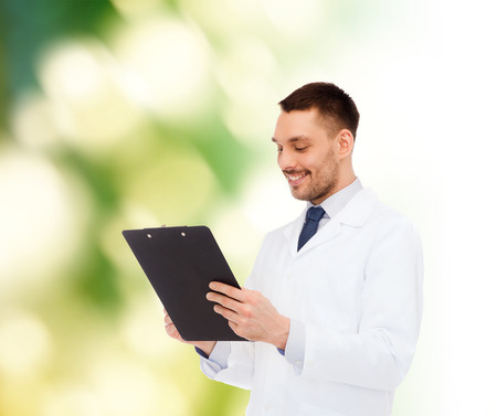 medicine, profession, and healthcare concept - smiling male doctor with clipboard writing prescription over white background photo