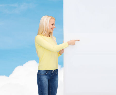 people, advertisement and sale concept - happy woman in sweater pointing finger to blank white board photo