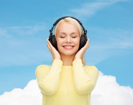 music and technology concept - smiling young woman with closed eyes listening to music with headphones photo