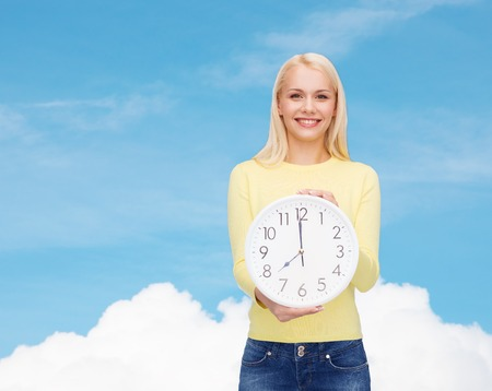 time, education and people concept - smiling young woman with wall clock showing 8 photo