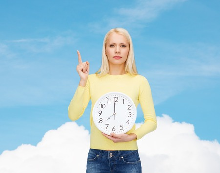 time, education and people concept - serious young woman with wall clock showing 8 and finger up photo