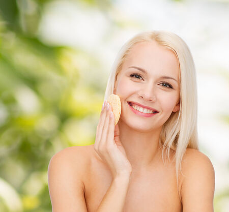 wash face: health, beauty and spa concept - beautiful woman with sponge Stock Photo