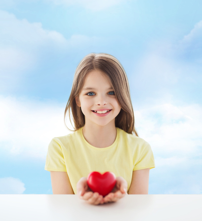love, charity, childhood and people concept - beautiful little girl sitting at table and holding red heart over cloudy sky background photo