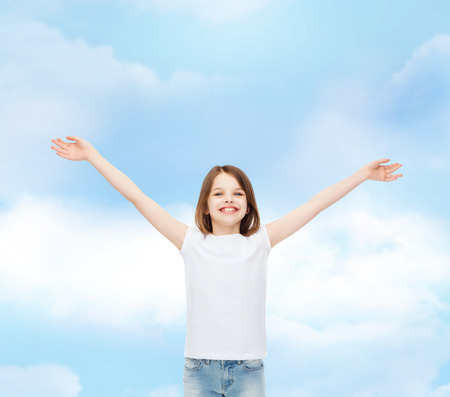stretched out: advertising, dream, childhood, gesture and people - smiling little girl in white t-shirt with stretched out arms over cloudy sky background