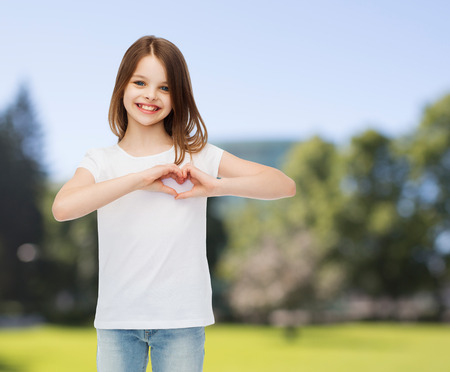 commercial tree care: advertising, childhood, nature, charity and people - smiling girl in white t-shirt making heart-shape gesture over green park background