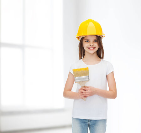 construction, building, childhood and people concept - smiling little girl in protective helmet with paint brush over white room background photo