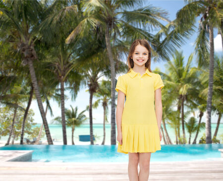 happiness, childhood and people concept - smiling little girl in yellow dress photo