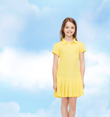 kids dress: happiness, childhood and people concept - smiling little girl in yellow dress