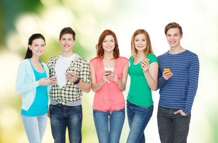 education and modern technology concept - smiling students with smartphones photo
