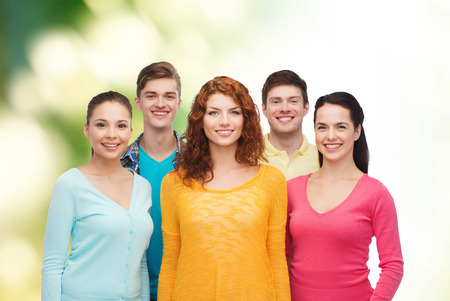 friendship, ecology and people concept - group of smiling teenagers standing over green background photo