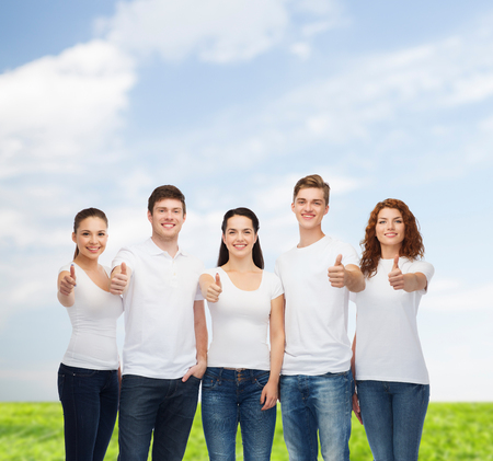 approvement: advertising, summer vacation, nature, friendship and people - group of smiling teenagers in white blank t-shirts showing thumbs up over blue sky and grass background