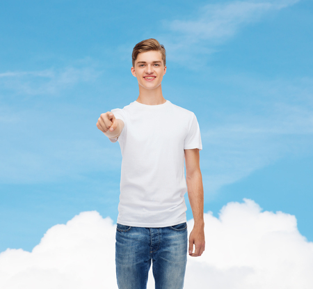gesture, advertising, dream and people concept - smiling young man in blank white t-shirt pointing at you over blue sky background photo