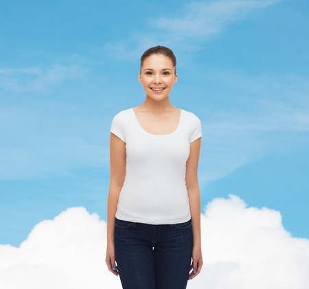advertising, dream and people concept - smiling young woman in blank white t-shirt over blue sky background photo