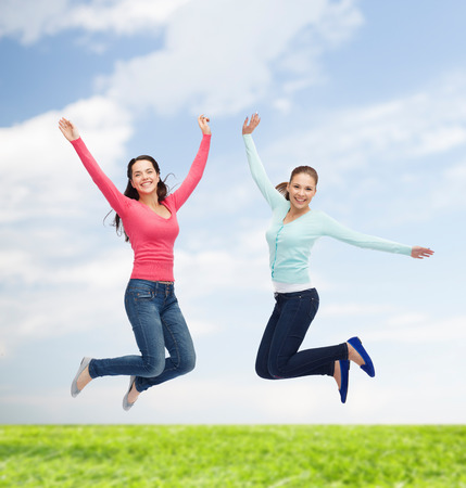 happiness, freedom, friendship, movement, summer and people concept - smiling young women jumping in air over natural background photo