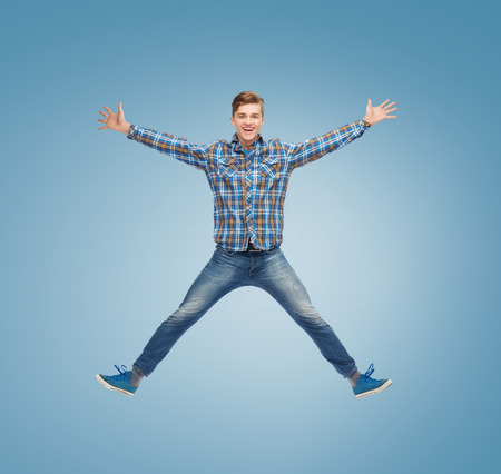 happiness, freedom, movement and people concept - smiling young man jumping in air over blue background photo