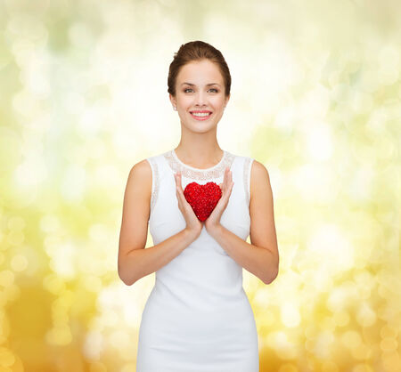 happiness, health, charity and love concept - smiling woman in white dress with red heart over golden lights background photo