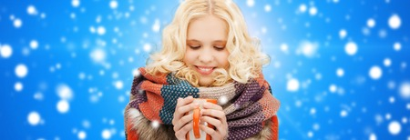 happiness, winter holidays, christmas, beverages and people concept - smiling young woman in warm clothes with cup over blue snowy background photo