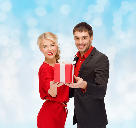 christmas, holidays, valentines day, celebration and people concept - smiling man and woman with present over blue lights background photo