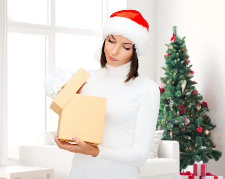winter, happiness, holidays and people concept - woman in santa helper hat with gift box over living room and christmas tree background photo