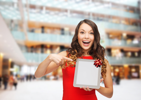 christmas, technology, present and people concept - smiling woman in red dress with blank tablet pc computer screen over shopping centre background photo