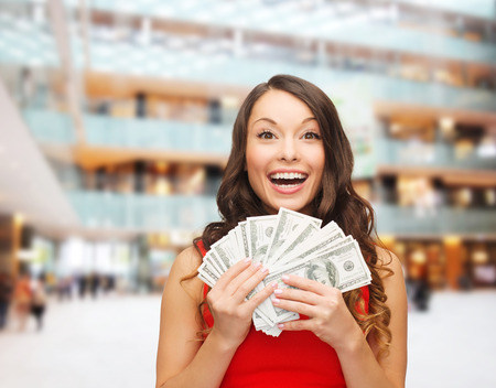 lottery win: holidays, banking, winning and people concept - smiling woman in red dress with us dollar money over shopping centre background Stock Photo