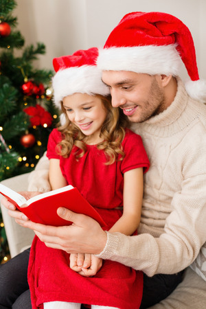 family, christmas, x-mas, winter, happiness and people concept - smiling father and daughter in santa helper hats reading book photo