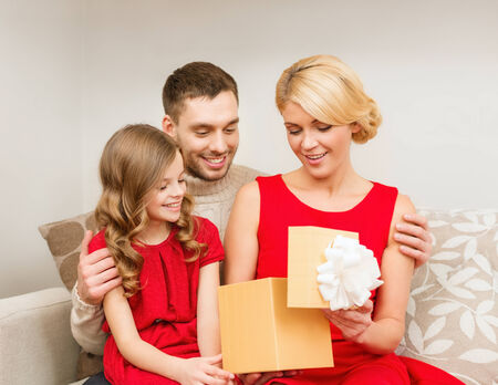 family, christmas, x-mas, winter, happiness and people concept - happy family opening gift box photo