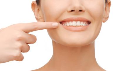歯科医療の概念 - 彼女の歯を指している美しい女性 写真素材