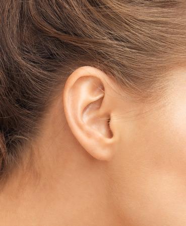 aretes: la audición, la salud, la belleza y el concepto de perforación - cerca de la oreja de la mujer Foto de archivo