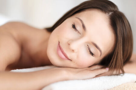 beauty and spa concept - beautiful woman with closed eyes in spa salon lying on the massage desk photo
