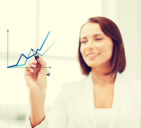 office, business, technology concept - businesswoman drawing graph in the air with marker photo