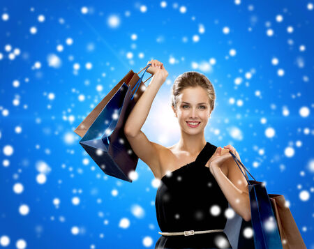 shopping, sale, christmas, people and holidays concept - smiling woman in evening dress with shopping bags over blue snowy background photo