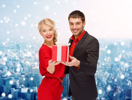 christmas, holidays, valentines day, celebration and people concept - smiling man and woman with present over snowy city background photo