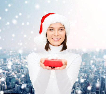 christmas, winter, happiness, holidays and people concept - smiling woman in santa helper hat with small red gift box over snowy city background photo