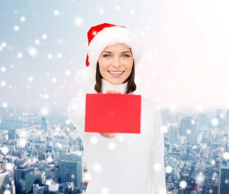 christmas, holdays, people, advertisement and sale concept - happy woman in santa helper hat with blank red card over snowy city background photo