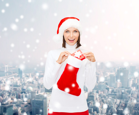 christmas, winter, happiness, holidays and people concept - smiling woman in santa helper hat with small gift box and stocking over snowy city background photo