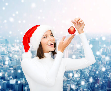 winter, people, christmas and happiness concept - woman in santa helper hat with christmas tree decoration ball over snowy city background photo