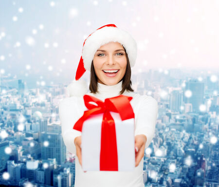 christmas, winter, happiness, holidays and people concept - smiling woman in santa helper hat with gift box over snowy city background photo